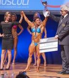 女性爱好健美者庆祝她的在阶段的冠军胜利 图库摄影