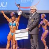 女性爱好健美者庆祝她的在阶段的冠军胜利 免版税库存图片