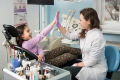 女性牙医和女孩耐心满意在对待牙在牙齿诊所办公室,微笑和做以后高五 库存图片