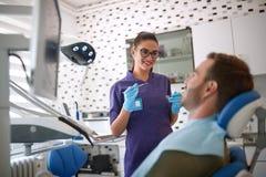 女性牙医起点与患者一起使用 免版税库存照片