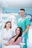女性牙医,微笑在检查以后的女性耐心和助理 免版税库存照片
