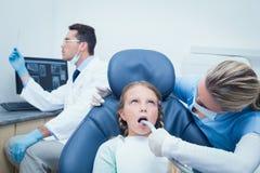女性牙医审查的女孩牙 免版税库存图片