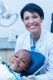 女性牙医审查的男孩牙画象  库存照片