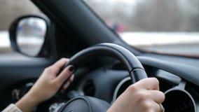 女性现有量特写镜头 女孩驾驶汽车,转动方向盘,汽车在行动4K缓慢的Mo 影视素材