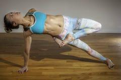 女性瑜伽模型Vasisthasana变异边板条变异 免版税库存照片