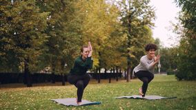 女性瑜伽辅导员在公园教开始学生老鹰姿势,快乐的女孩做差错和笑 股票视频