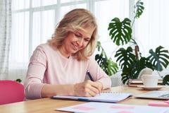 女性用意想不到的微笑饮用的咖啡,当写时 免版税库存照片