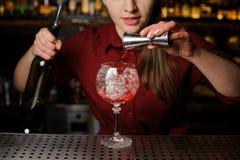 女性男服务员倾吐苦涩入做的Aperol s一块玻璃 免版税库存图片