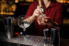 女性男服务员冰块为做鸡尾酒做准备 免版税库存图片