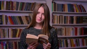 女性白种人学生看书和观看入在书架背景的照相机 股票录像