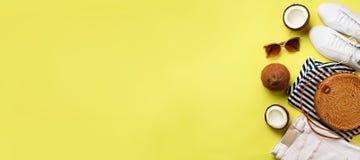 女性白色运动鞋、牛仔裤、镶边T恤杉、藤条袋子、椰子和太阳镜在黄色背景与拷贝空间 免版税图库摄影