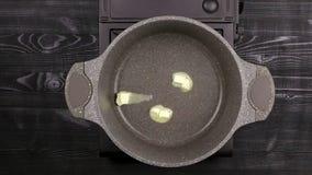 女性的厨师手在煎锅投入了黄油 油融解和传播片断底部的热表面上 一部分的proces 股票视频