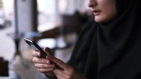 女性的手withblack智能手机瞄准的英尺长度  使用她的智能手机,关闭咖啡馆的回教妇女,聊天 股票录像