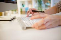 女性的特写镜头在办公室递键入在膝上型计算机键盘 免版税库存照片