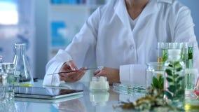 女性皮肤病学家测试新的护手霜,申请在皮肤用金属棍子 库存图片