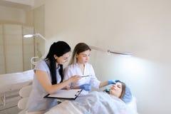 女性眼眉纹身花刺大师教女学生与c一起使用 库存照片