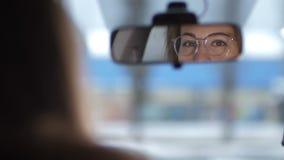 女性眼睛的反射在汽车的前面镜子的 与玻璃的布朗眼睛调查照相机4K缓慢的Mo 股票视频
