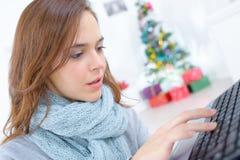 女性研究在圣诞节时间的膝上型计算机 免版税图库摄影