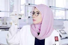 女性科学家拿着一个小瓶 库存照片