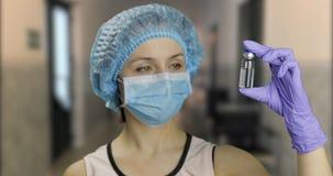 女性科学家藏品细颈瓶在手中在医院,疗程接种 免版税库存图片