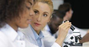 女性科学家解释实验的辅助结果与在研究员队的显微镜一起使用现代的 股票录像