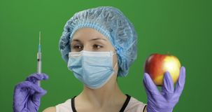 女性科学家选择有医学或苹果的注射器 库存照片