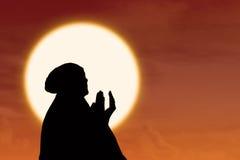女性穆斯林剪影祈祷在日落 免版税库存照片