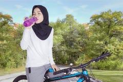 女性穆斯林在公园喝在自行车的水 库存照片