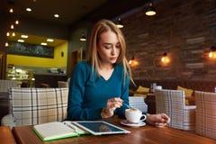 女性等待再开始片剂计算机持续工作在网络 免版税库存照片