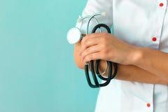 女性篡改拿着在浅兰的背景的` s手听诊器 免版税库存图片