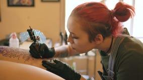 年轻女性红发在客户的腿的纹身花刺艺术家刺字的图片在剪影的在演播室户内 影视素材