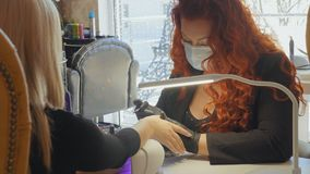女性红色做客户的指甲盖的一个温泉做法 免版税库存图片