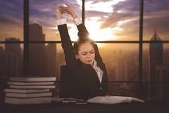 女性经理在劳累过度以后舒展胳膊 库存图片