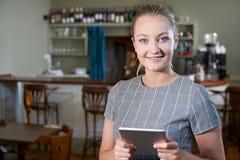 女性经理画象在有数字式片剂的餐馆 库存照片