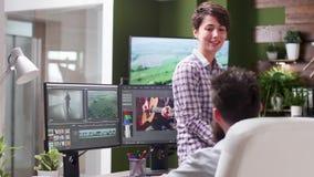 女性编辑中等移动式摄影车射击谈话与同事 股票视频