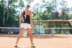女性网球员充分的身体画象行动的在室外的网球场 从后面的看法 免版税库存照片