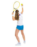 女性网球员服务球。背面图 免版税图库摄影