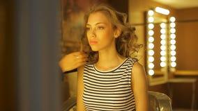 女性美发师做一个华美的女孩的一种典雅的长的宽松发型 股票录像