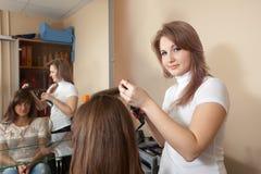 女性美发师在沙龙的头发工作 免版税库存照片