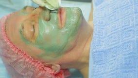 女性美容师从人s面孔去除一个治疗泥面具与化装棉 侧视图 影视素材