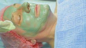 女性美容师从人s面孔去除一个治疗泥面具与化装棉 股票录像