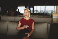 女性考虑事好在她的手机的读的正文消息前,当坐在现代咖啡店时, 库存图片
