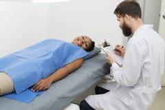 女性耐心说谎在床上,当Holding Clipboard医生时 库存图片
