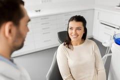 女性耐心谈话与牙齿诊所的牙医 库存图片