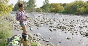 年轻女性背包徒步旅行者投掷的石头在河 影视素材