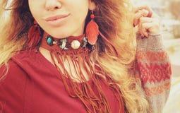 女性脖子和耳朵有boho项链和耳环的有红色羽毛和棕色皮革的,手工制造首饰 免版税图库摄影