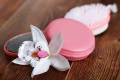女性脚、肥皂和兰花的桃红色轻石在木背景 免版税图库摄影