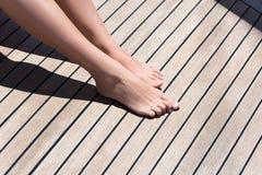 女性脚特写镜头在一个木甲板的 晒日光浴在船 图库摄影