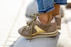 女性脚特写镜头在米黄运动鞋的 时兴的妇女 库存照片