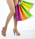 女性腿和多彩多姿的购物袋 免版税库存照片